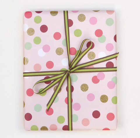 gift wrapped present with pink polka dot paper and gold ribbon