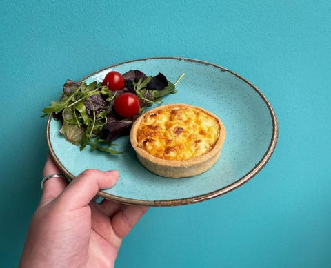 hand holding up a plate of quiche with salad from mhor coffee in perth scotland