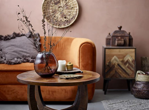 wooden coffee table with vase sat in front of an orange sofa