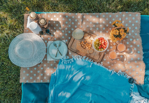 picnic blanket with book, hat, plates, cutlery, food and a hat
