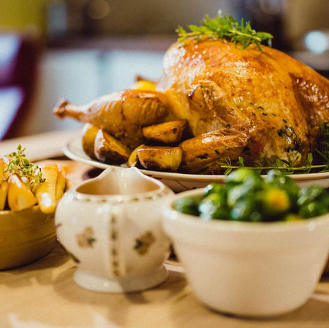 roast chicken with a jug of gravy and bowl of brussel sprouts on a table from hugh greirsons organic farm perthshire
