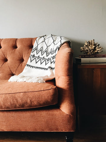 autumnal orange couch with rustic blanket in a living room