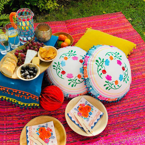 pink picnic rug with cushions, plates, snacks and drinks