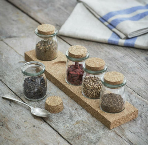 cork spice rack with five individual glass jars filled with spices on a table