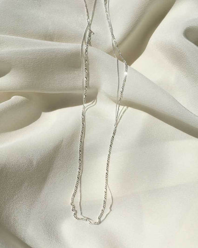 Figaro link chain (Sterling Silver) and Whisper Chain for layering by Sit & Wonder, shown on an ivory silk background