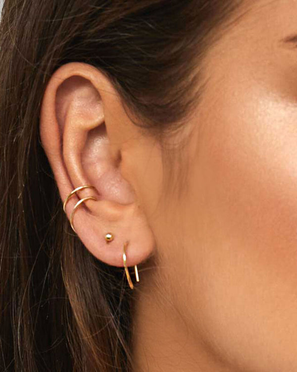 Model wearing 9k Yellow Gold stacking earrings by Sit & Wonder. Arc Earrings, Ball Stud and Fine Ear Cuffs pictured here.