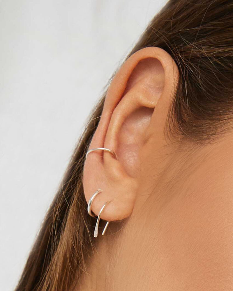Model wearing Sterling Silver stacking earrings by Sit & Wonder. Arc Earrings, Mini Hoops and Fine Ear Cuff pictured here.