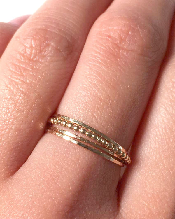 Whisper rings and beginnings ring shown in a dainty ring stack on a model's hand