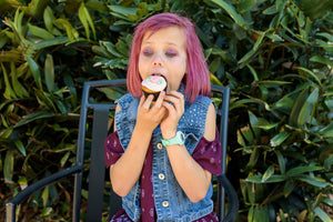 Pink-haired girl eating a No Guilt Baking Company Cupcake!