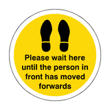 Please Wait Until Person In Front Has Moved Floor Sticker - Yellow | Safety-Label.co.uk