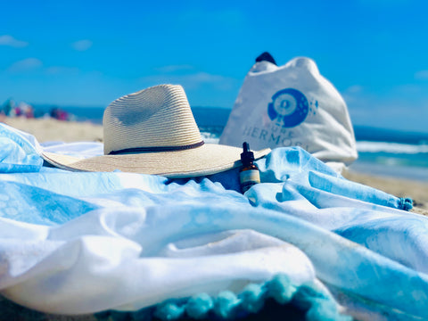 This bottle of CBD oil, sitting on a beach blanket with a sun hat and Pure Hermosa beach bag, contains the healing benefits of CBD and Hemp Extract Oil.