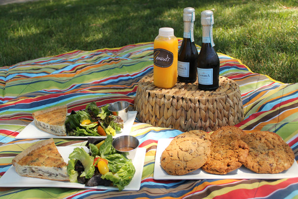 2 plates of Quiche w/ salad, 1 plate of 6 cookies, 1 bottle of OJ, and 2 individual sized Proseccos, on a picnic blanket.
