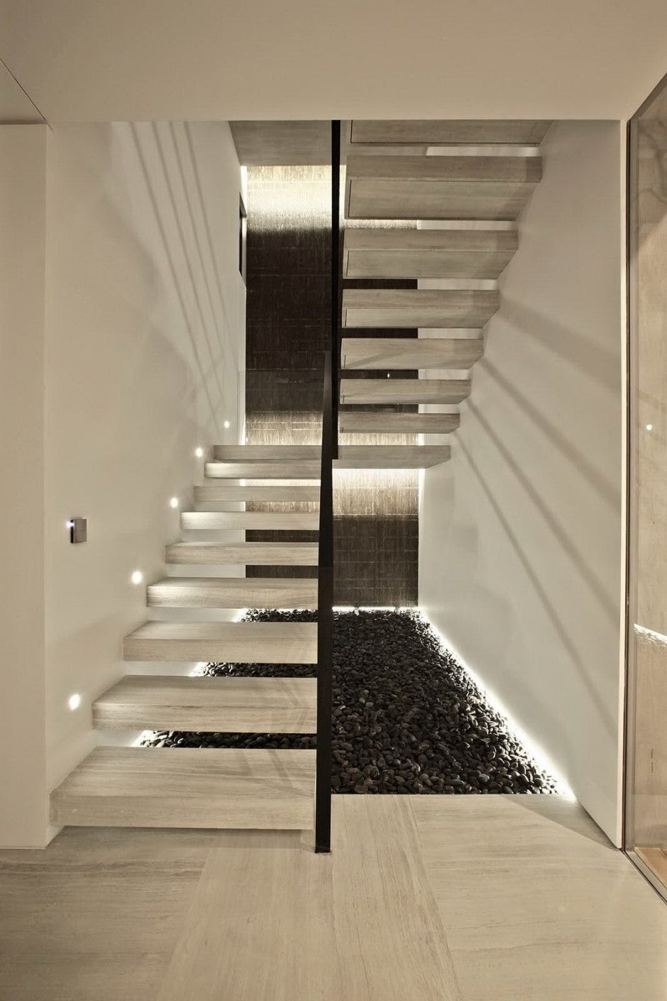 On the wall run from ceiling to floor as well as the stones or pebbles underneath the staircase add a zen like and very modern appeal to the house