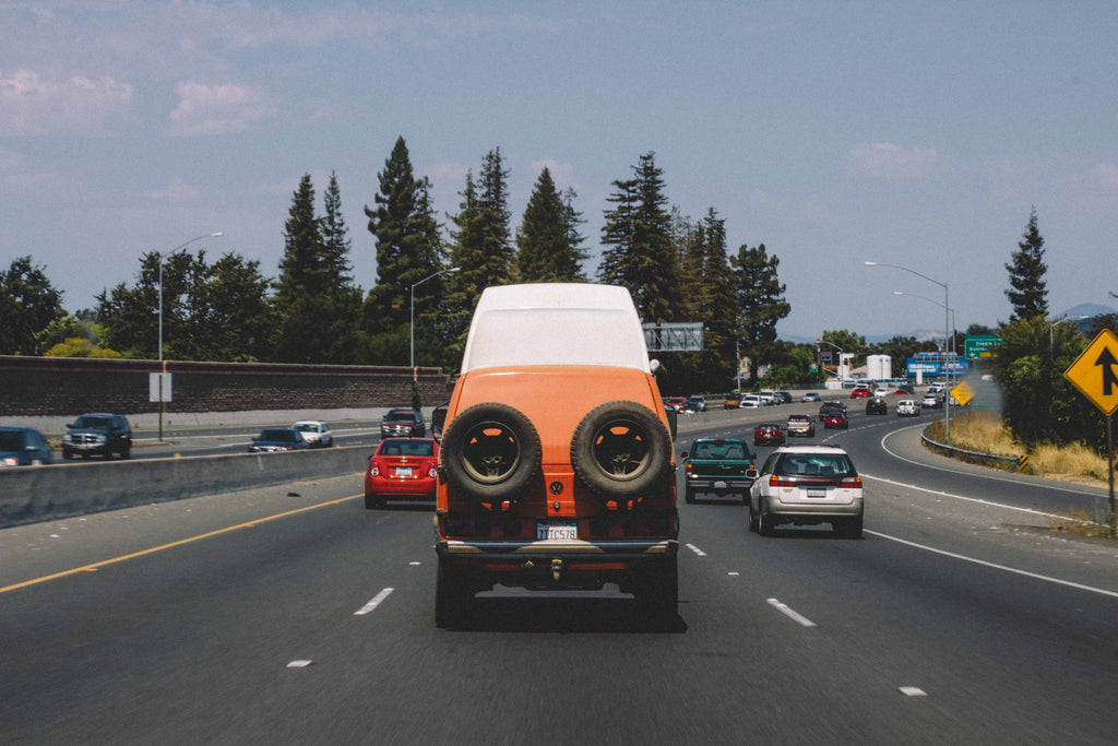 An orange van driving north on highway 101 in California.