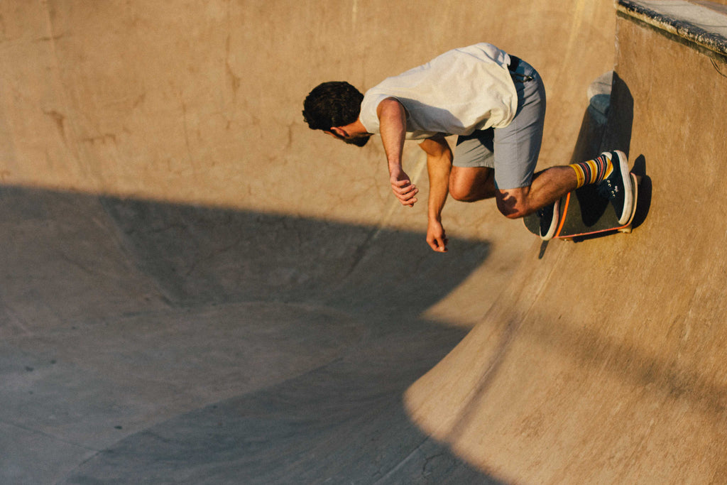 Skateboarder doing backside turn in a bowl.