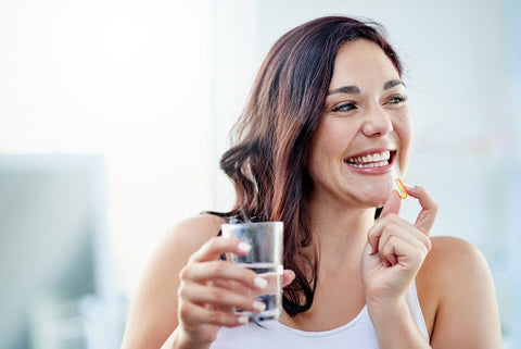 Young woman smiling with a glass of water and taking vitamins that help with memory