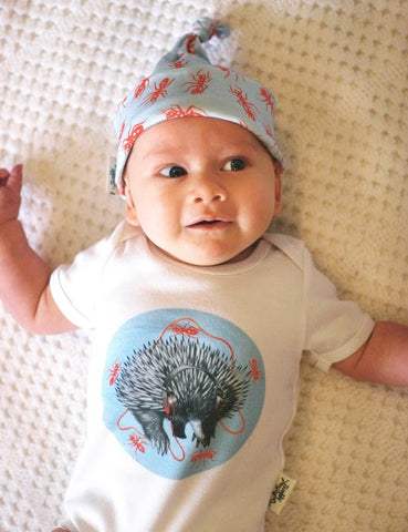 made in australia. Unique baby onesie made from 100 percent organic cotton. Echidna print on soft pastel blue background with red fire ants and head phones. funky print for little boy