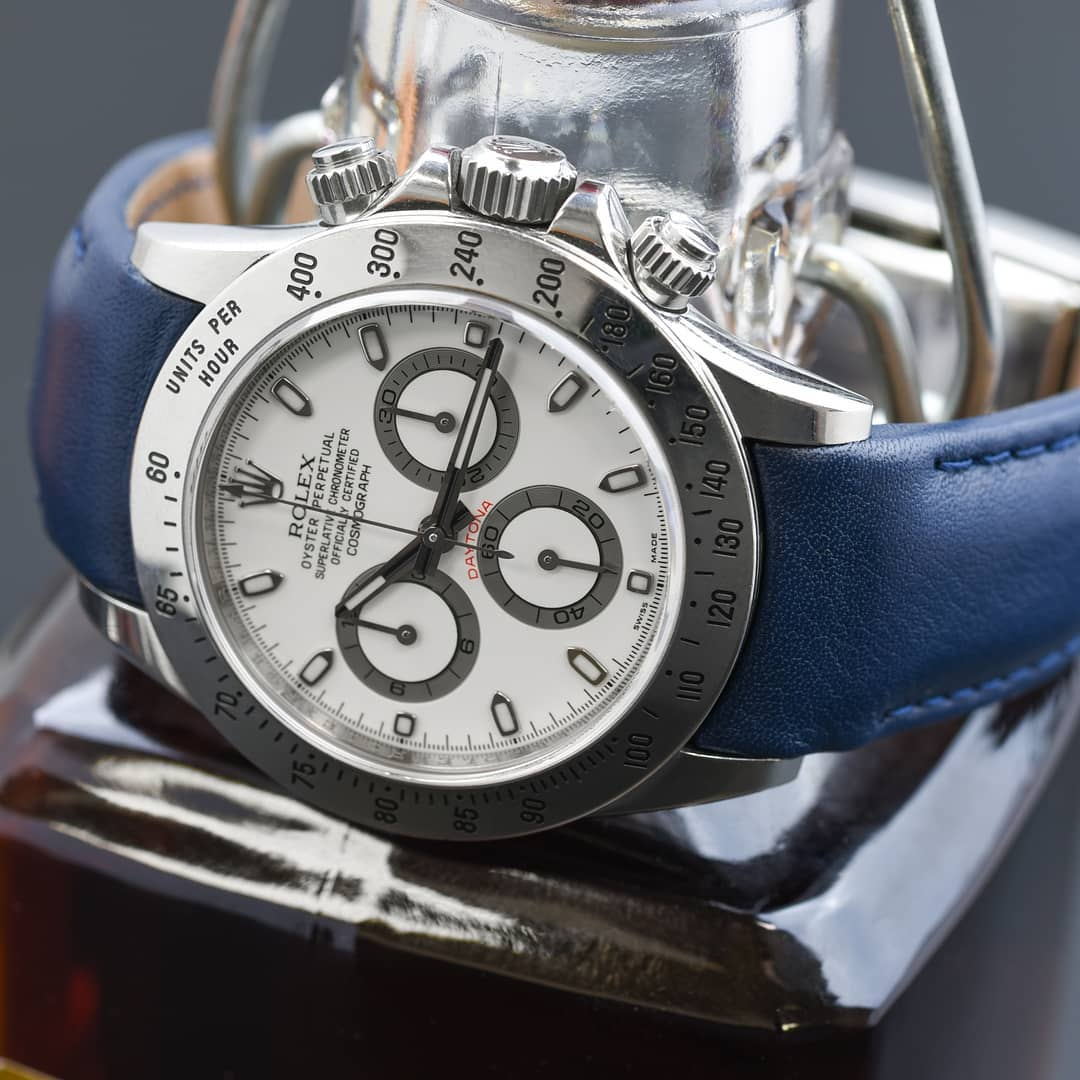 blue leather curved end strap on a white dialed rolex daytona watch