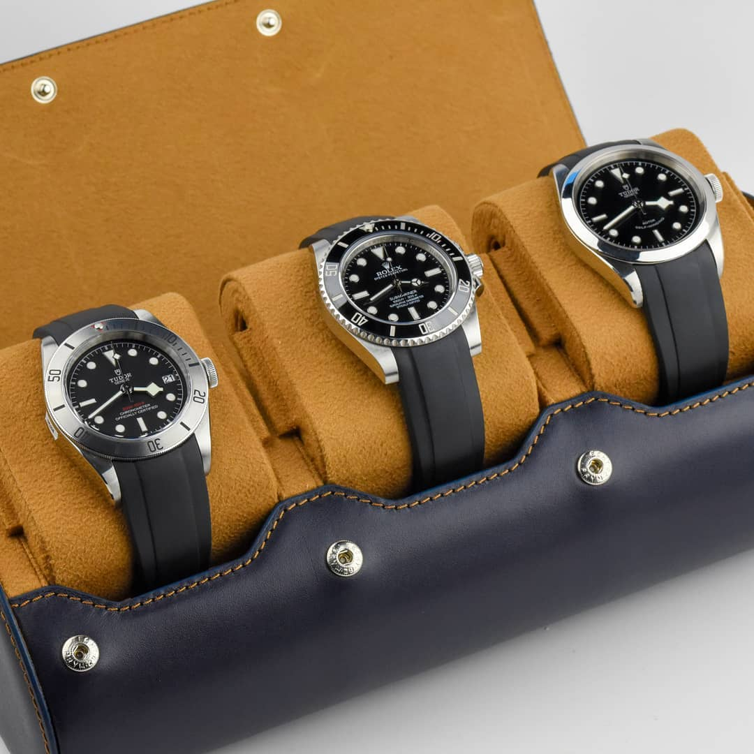 3 watches in a leather watch roll rolex and tudor