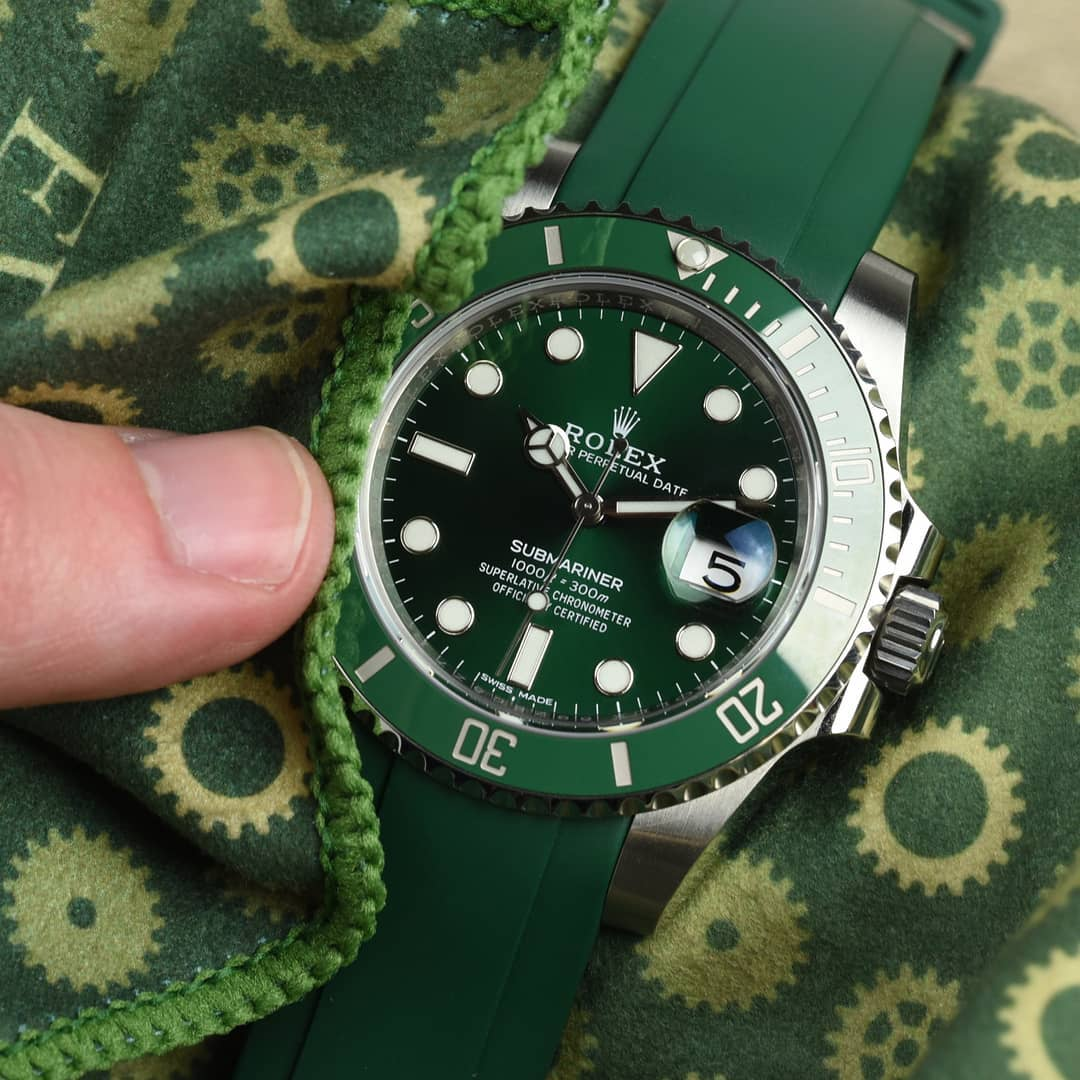 rolex hulk on green rubber strap being cleaned by a cleaning cloth
