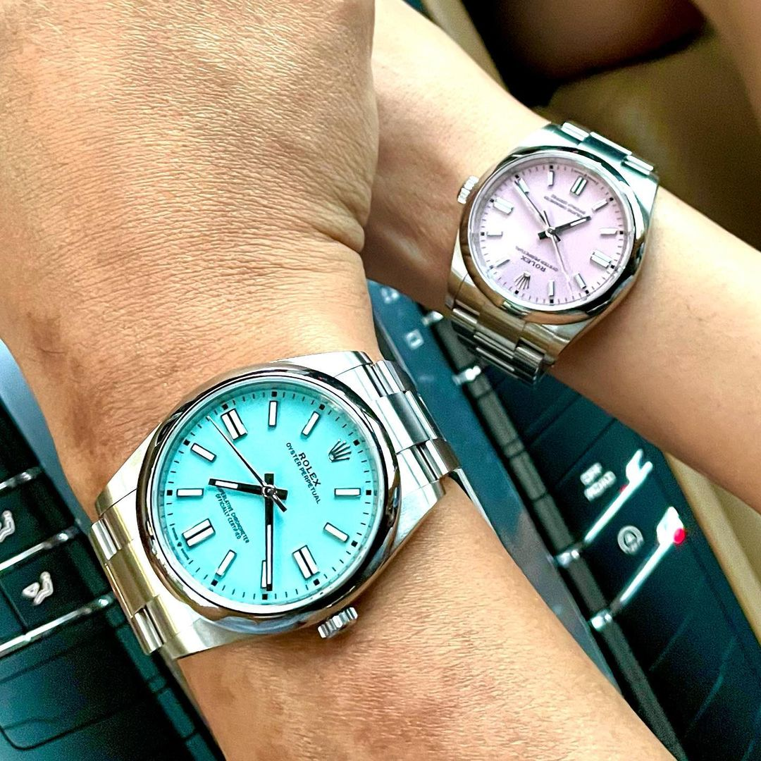 rolex oyster perpetual 41 mm in turquoise blue next to a candy pink rolex oyster perpetual in 36 mm