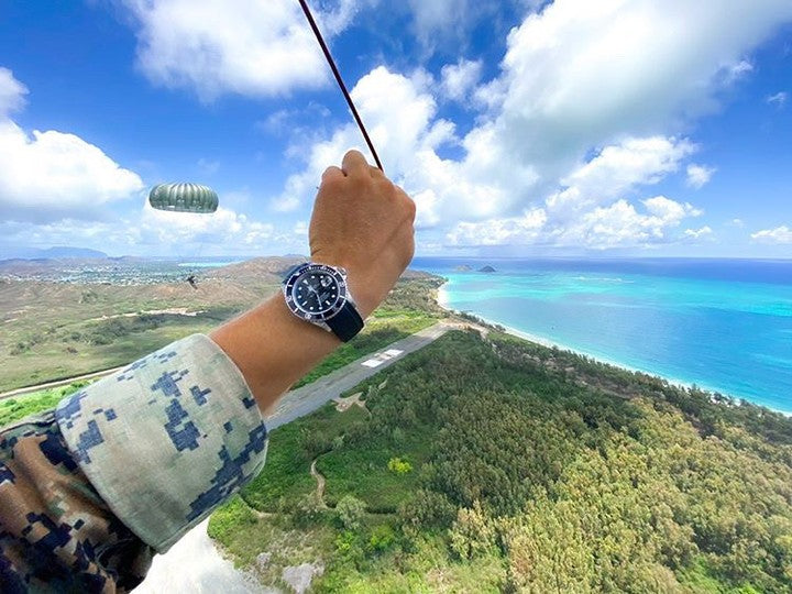 rolex submariner on rubber strap on arm while sky diving