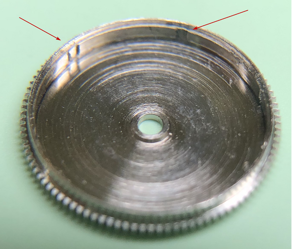 Watch movement spring barrel showing notches to prevent overwinding