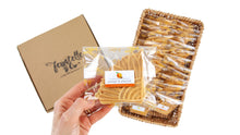 Load image into Gallery viewer, Packets of ferratelle or pizzelle of orange & almond flavour in a basket