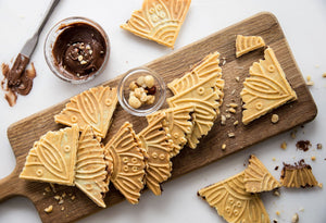 Ferratelle or pizzelle filled with chocolate and hazelnut spread served on a board