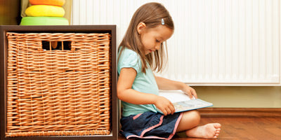 Little girl reading in front of a warm radiator