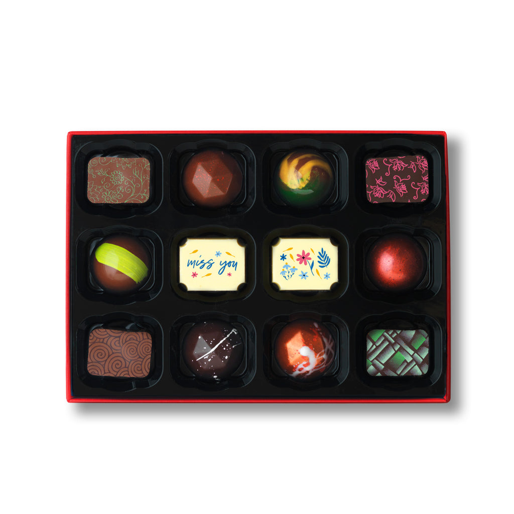 Luxury chocolate gift box of 12 chocolates for special occasions.  Selection of 12 milk, dark, and white chocolates. The box includes 2 Miss you chocolates, popular hand painted and caramel chocolates