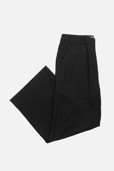 Black trouser style pant with a wide elastic waist, relaxed silhouette, and ankle grazing length