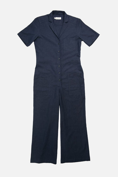 Utility inspired jumpsuit with a lapel collar, button front, patch pockets, and waist adjustment tabs