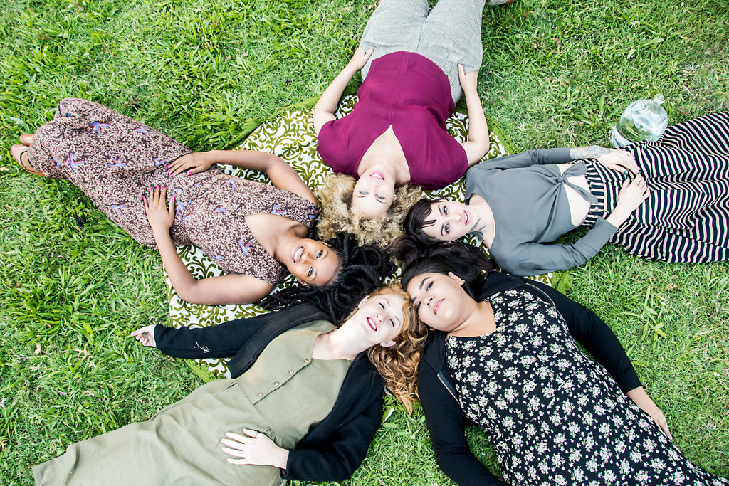 group of women laying in the grass in field days fall collection