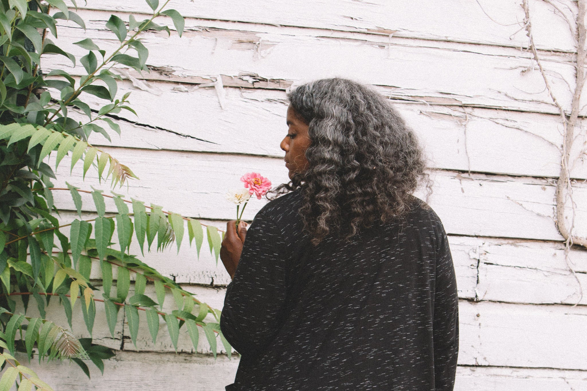 back side of woman wearing a cardigan with a flower in her hand