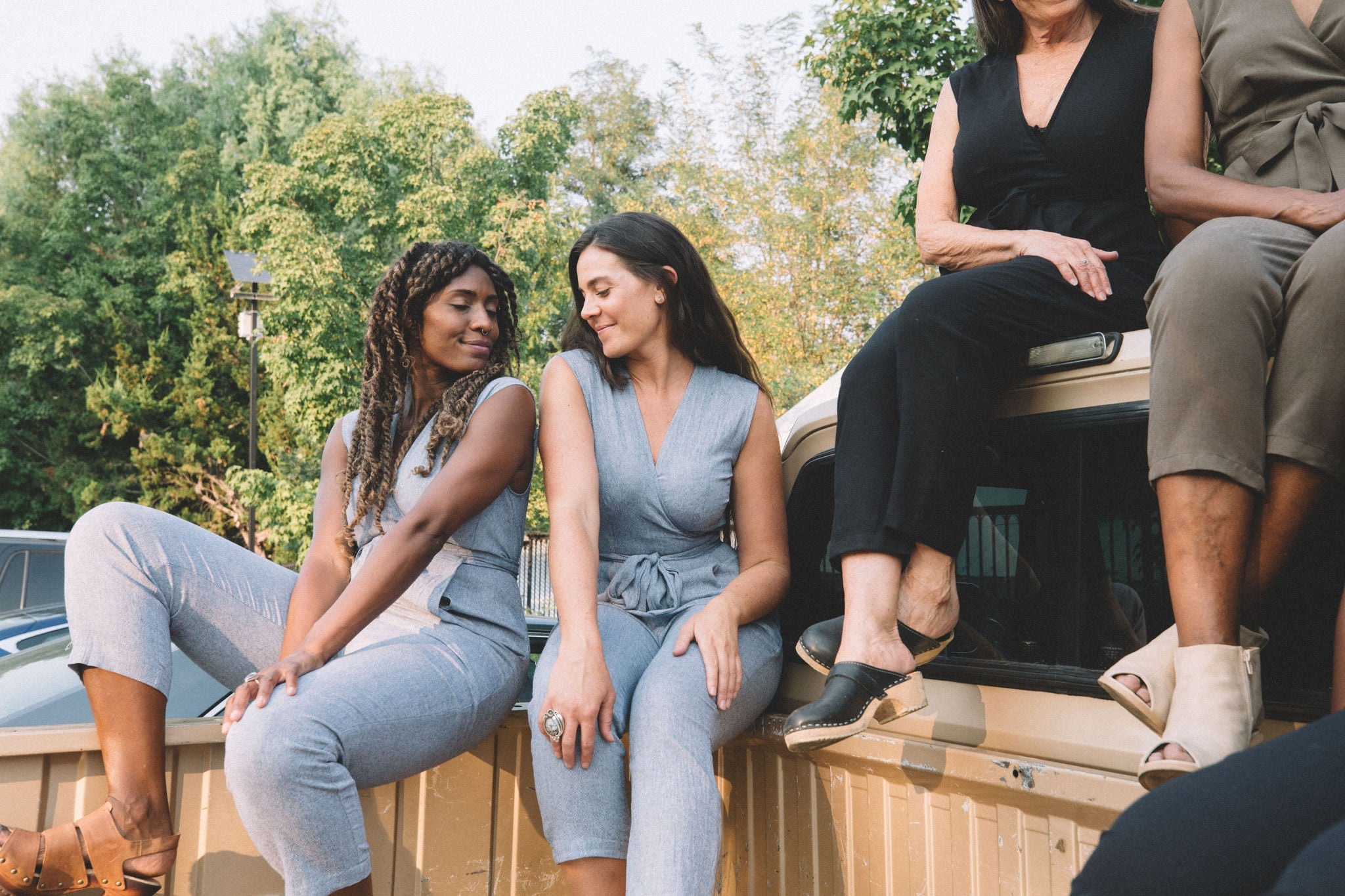 women sitting in the back of a truck with high waisted jumpsuits on