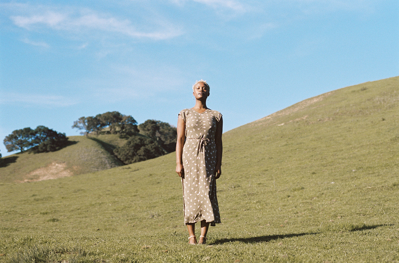 black woman wearing a olive dress on a hill top