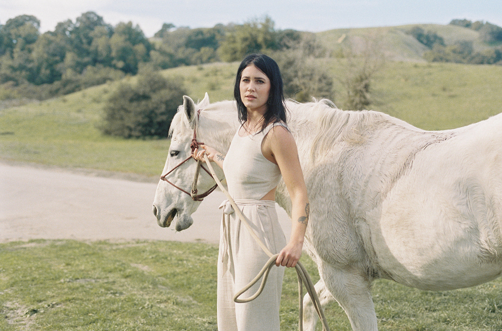 white horse with a white man wearing a cream jumpsuit