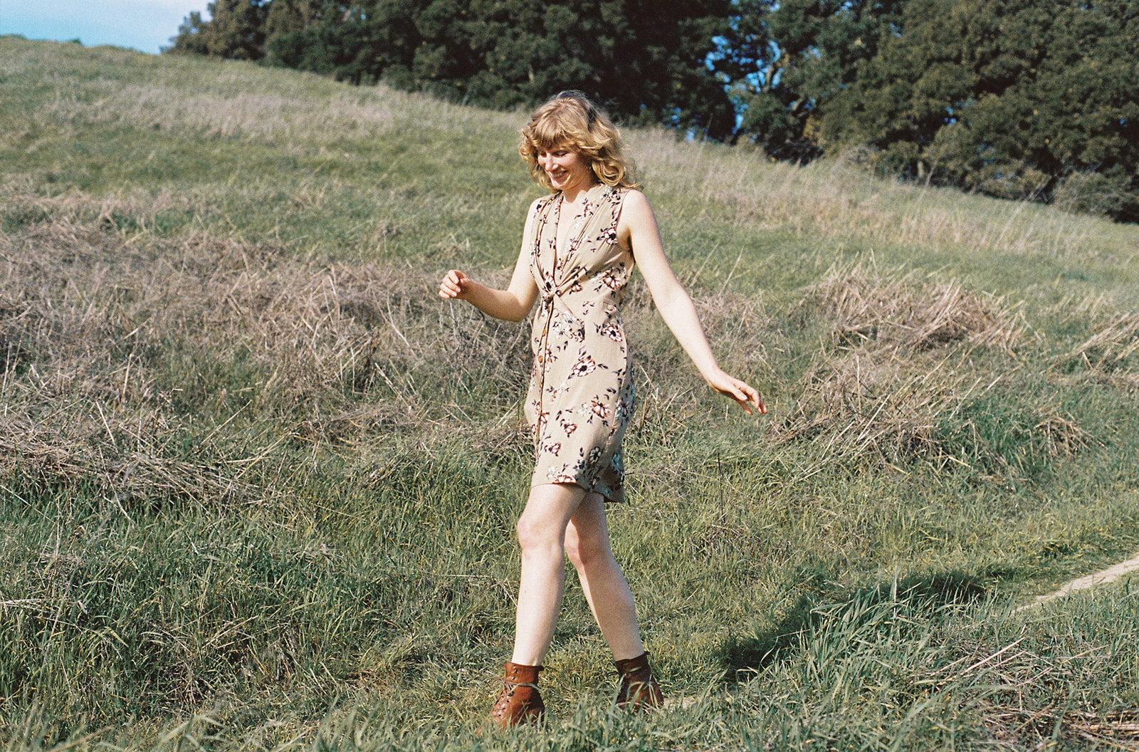 woman in tan floral dress skipping