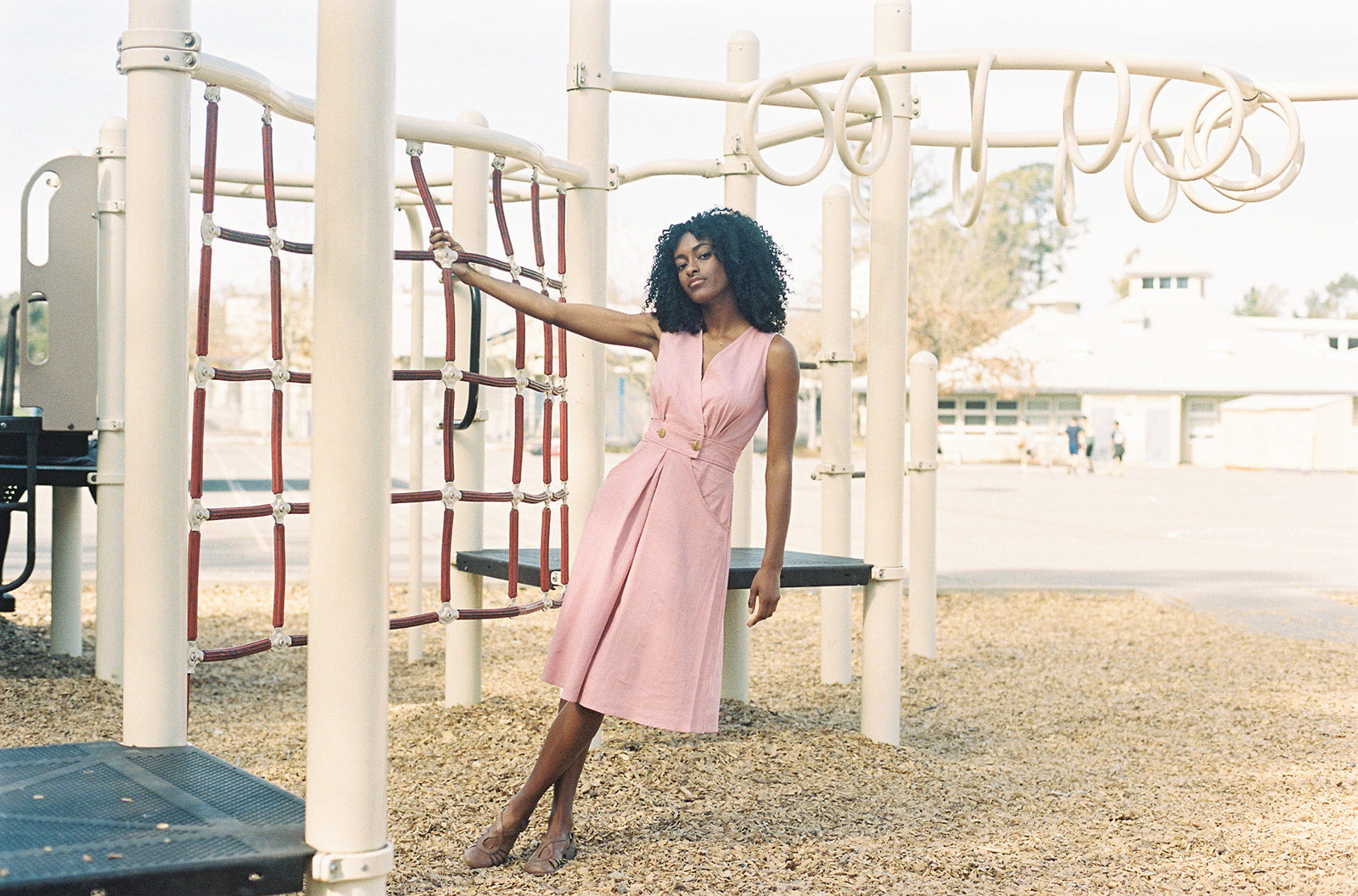 pink dress on a play ground worn by black model