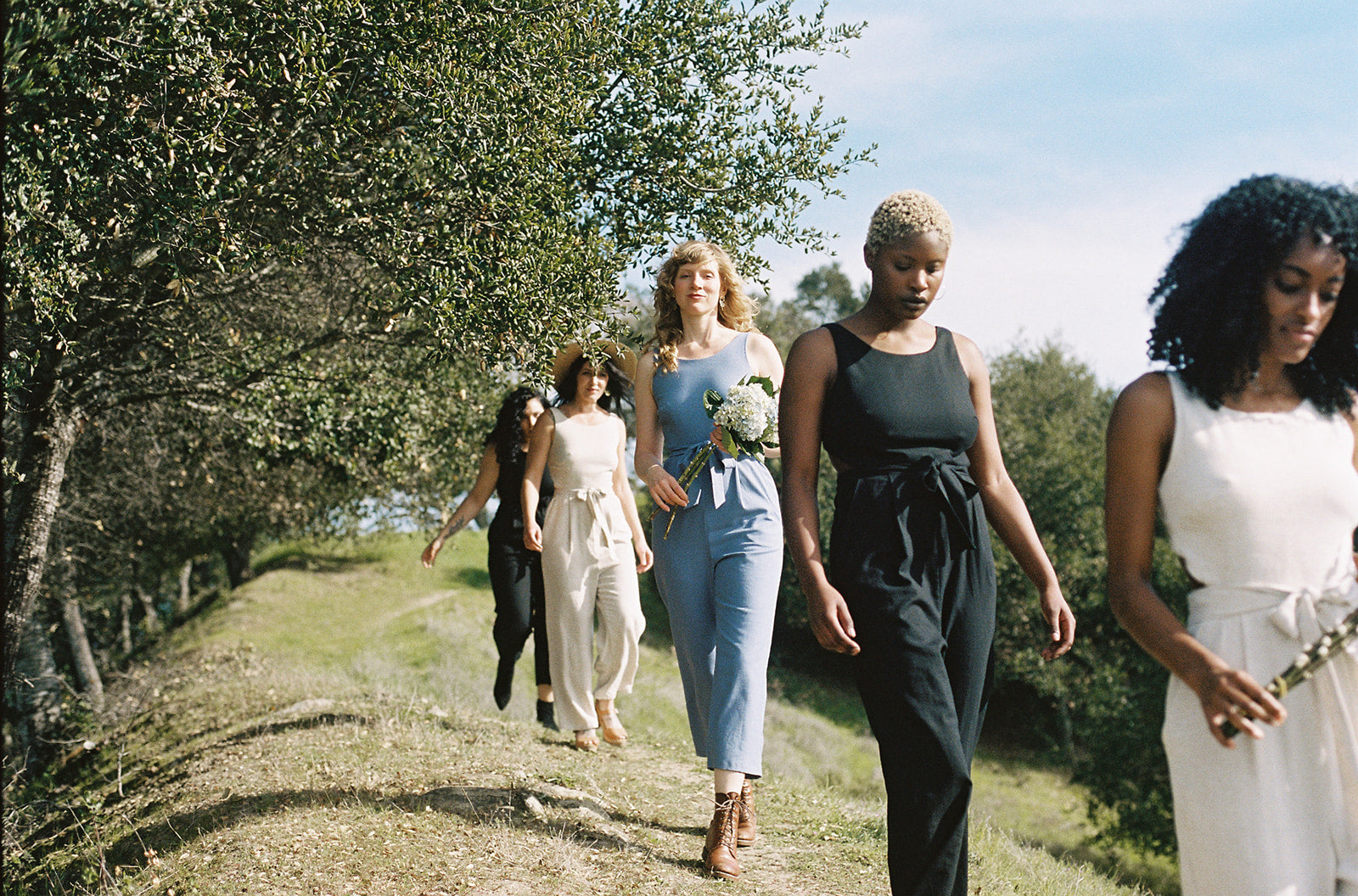 group of women walking in jumpsuits