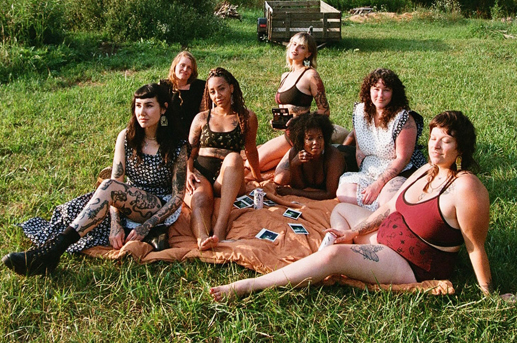 collaboration of women designers in a field on a blanket wearing eachothers designs