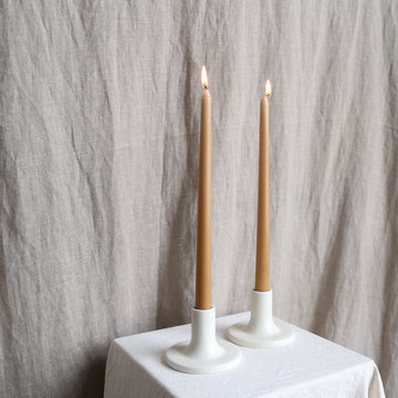 Pair of honey taper candles in white holders available at Rook & Rose.