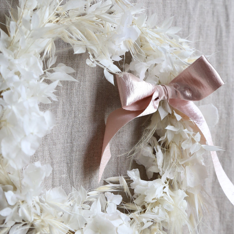 White dried floral wreath with pink bow available at Rook & Rose.
