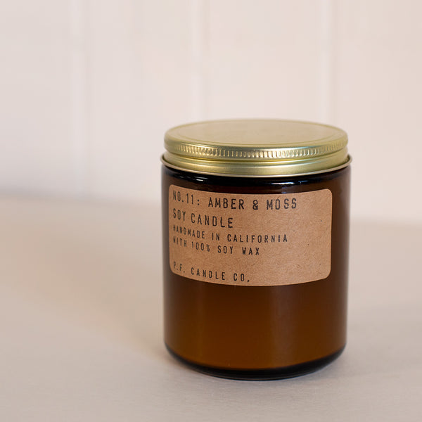 Amber and moss scented candle in an amber glass container by P.F. Candle Co. available at Rook & Rose in Victoria, British Columbia, Canada