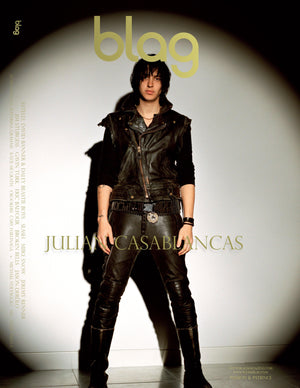 BLAG magazine Julian Casablancas cover, photography by Sarah J. Edwards. Produced by Sally A. Edwards and Sarah J. Edwards. Julian stands in front of a white wall, lit by a spot light. He wears black leather vest, trousers and sweater. With black leather boots.