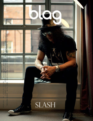 BLAG magazine Slash cover. Guns N Roses guitarist Slash is photographed sitting in a window, he wears his trademark top hap and sunglasses, along with black t-shirt, jeans and converse shoes. Photography by Sarah J. Edwards, Produced by Sally A. Edwards and Sarah J. Edwards