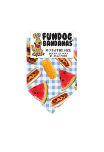 Various picnic foods are displayed on a blue and white checkered picnic blanket on a one size fits most dog bandana.