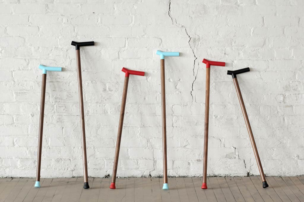 Arrangement of six modern walking canes leaning against white wall