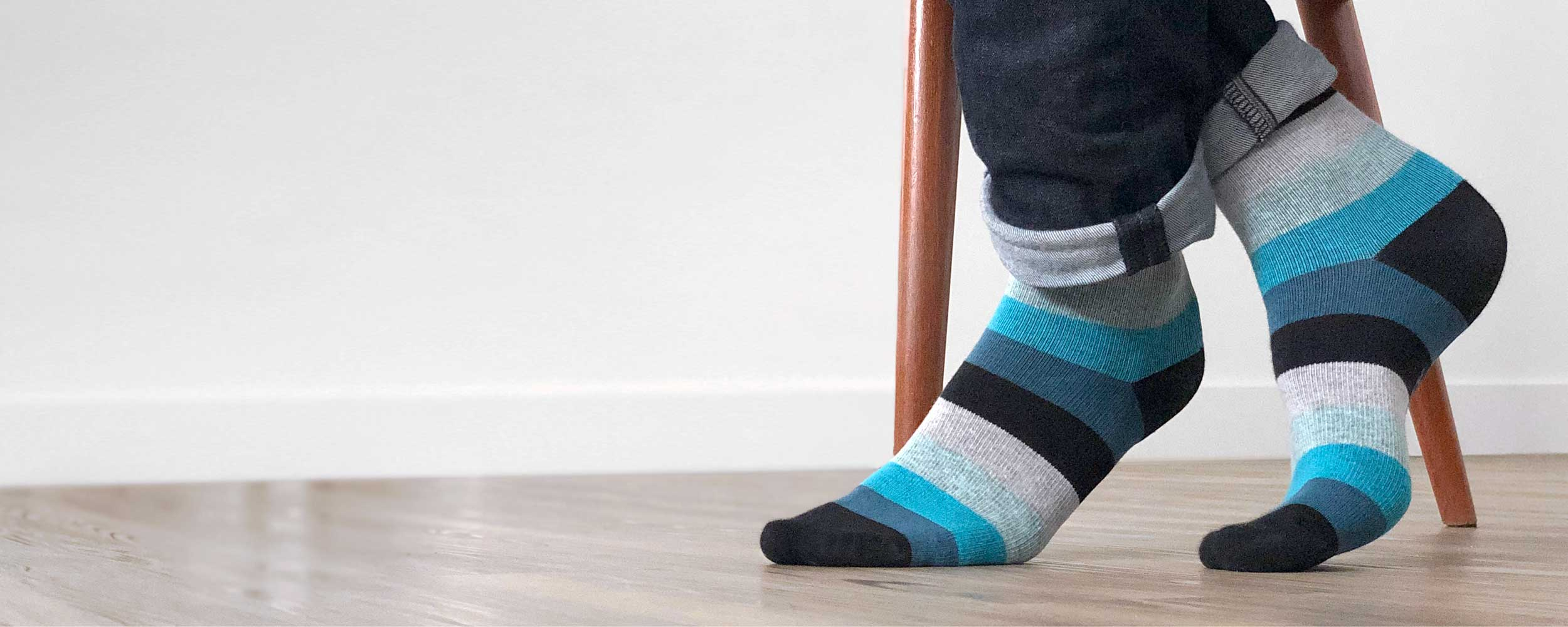 Man's feet with blue and black striped compression stockings